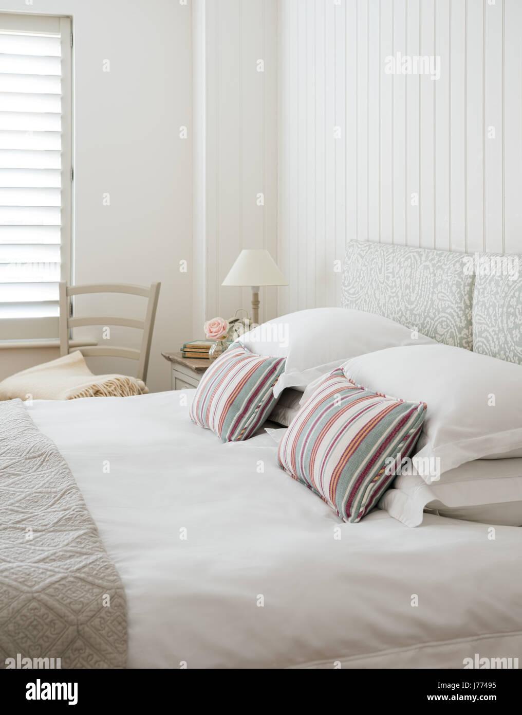 Stripey cojines hechos en Clarke & Clarke's Mitra tejido en Sage en cama con cabecero de Paisley. Imagen De Stock