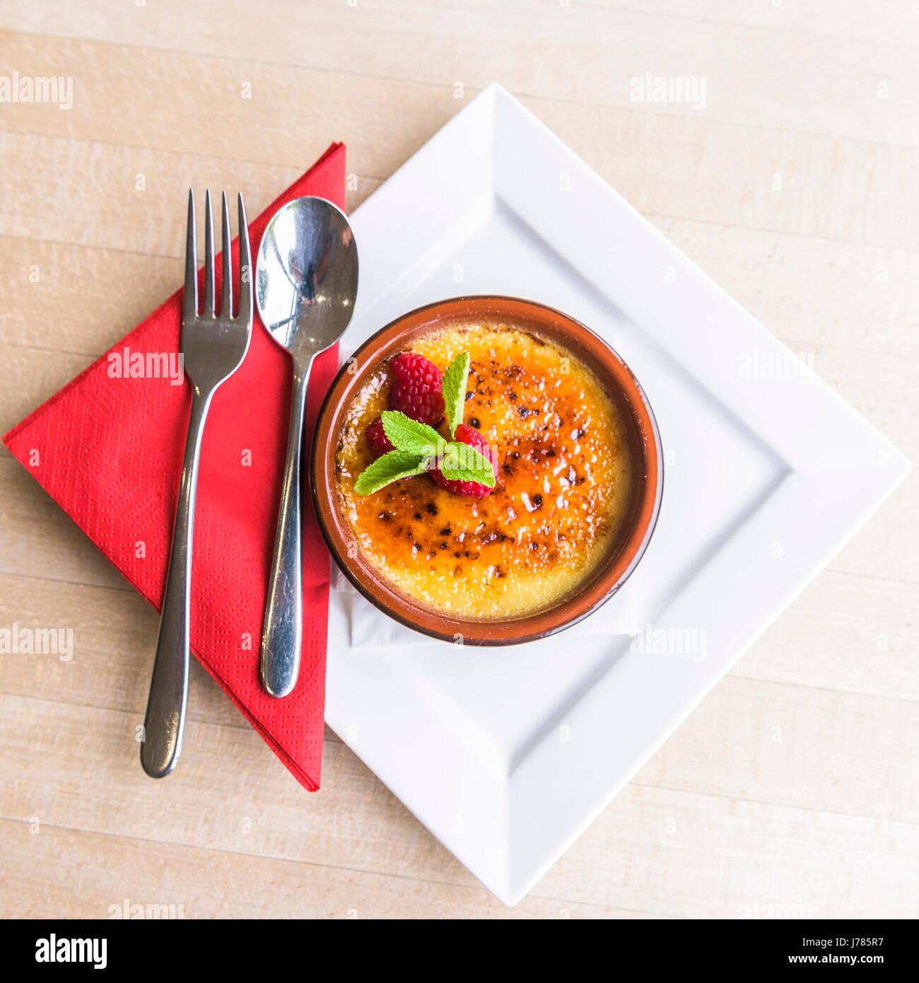 Un Creme Brulée servido en un restaurante; el postre; Alimentos;; budín dulce; cubertería; Rasberries; Imagen De Stock