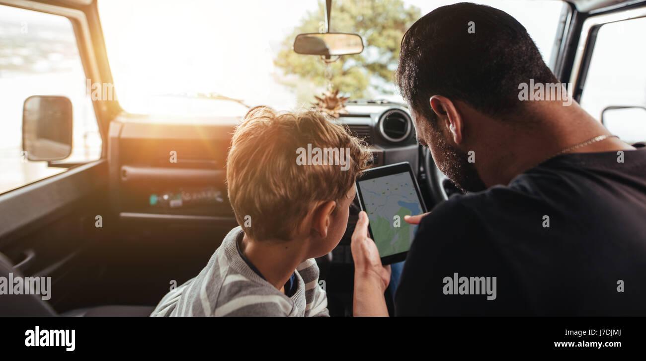 Cerrar vista trasera de padre e hijo mirando el mapa sobre la tableta digital mientras viaja en coche. Familia buscando Imagen De Stock