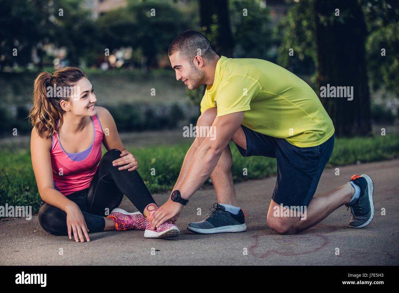 El hombre ayuda a la mujer con la rodilla lesionada en la actividad deportiva Imagen De Stock
