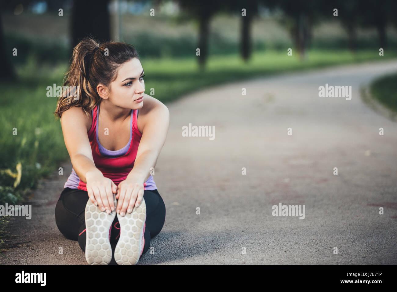 La mujer es el estiramiento antes de correr. Fitness y concepto de estilo de vida. Foto de stock