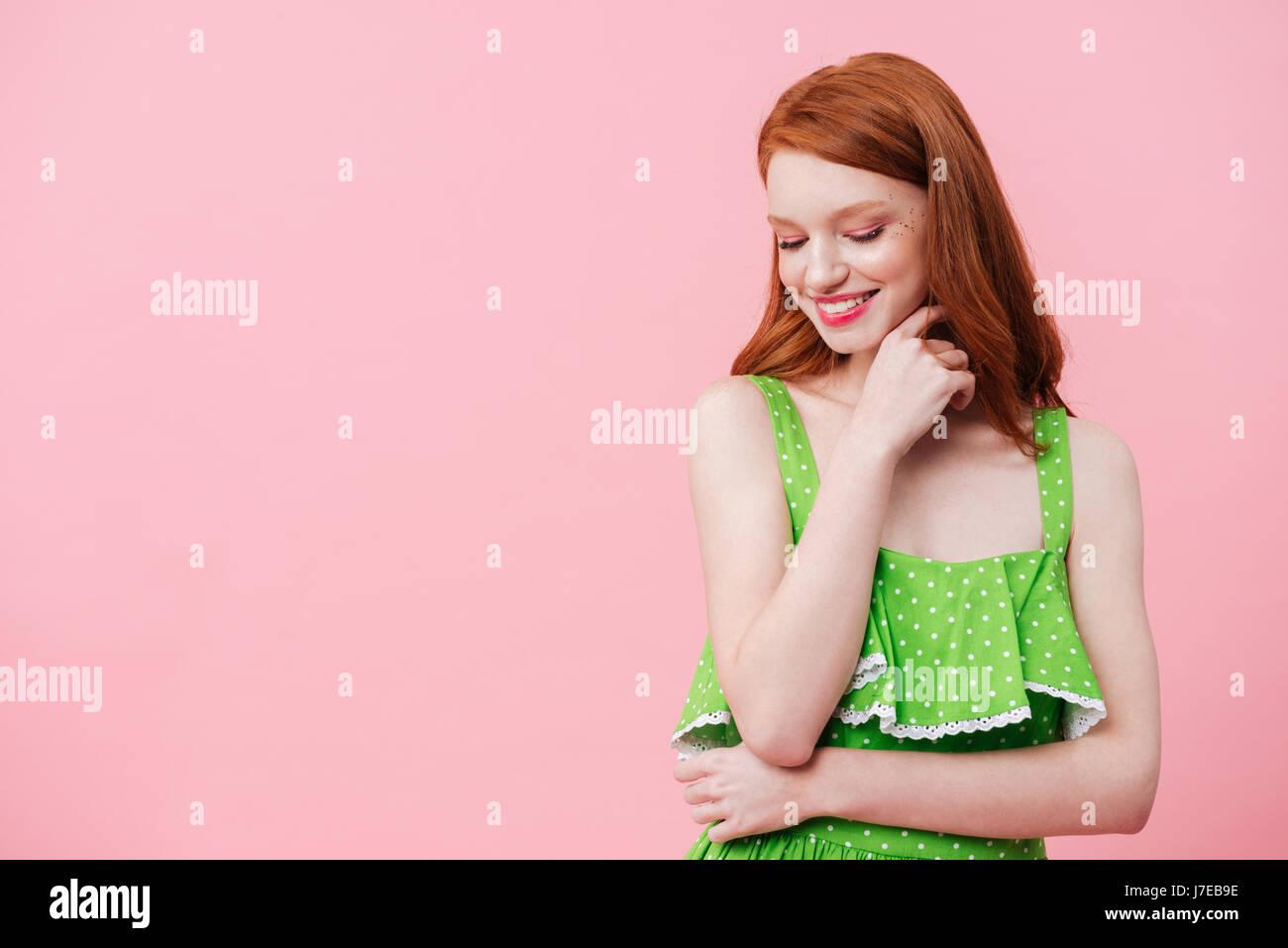 Retrato de joven pelirroja mujer vistiendo vestido verde y mirando hacia abajo Imagen De Stock