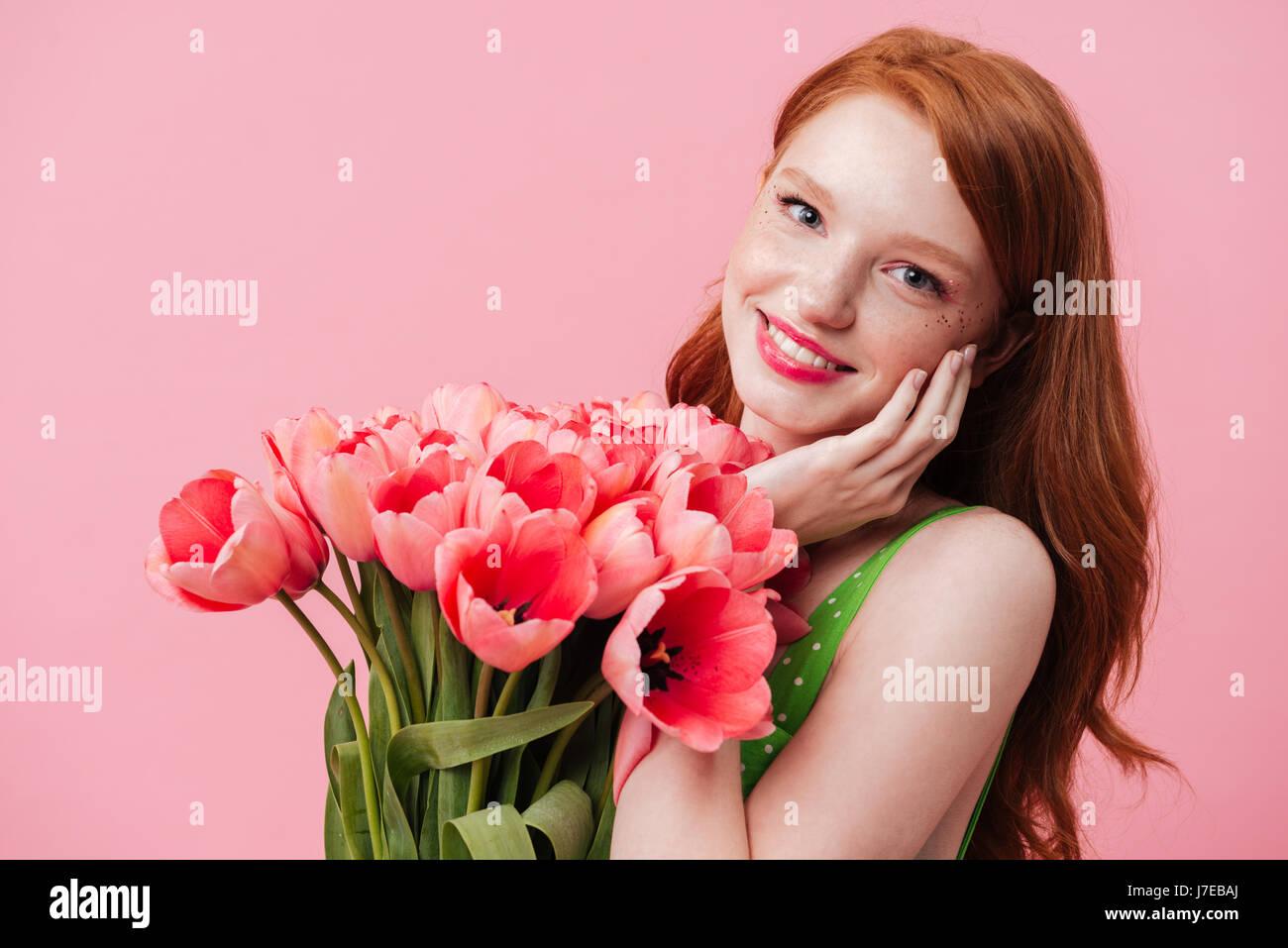 Hermosa joven mujer sonriente sosteniendo los tulipanes cerca de cara aislado Imagen De Stock