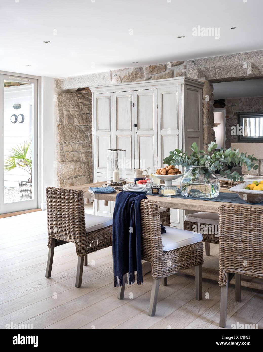 Amplia cocina comedor con paredes de granito expuesta, ratán sillas ...