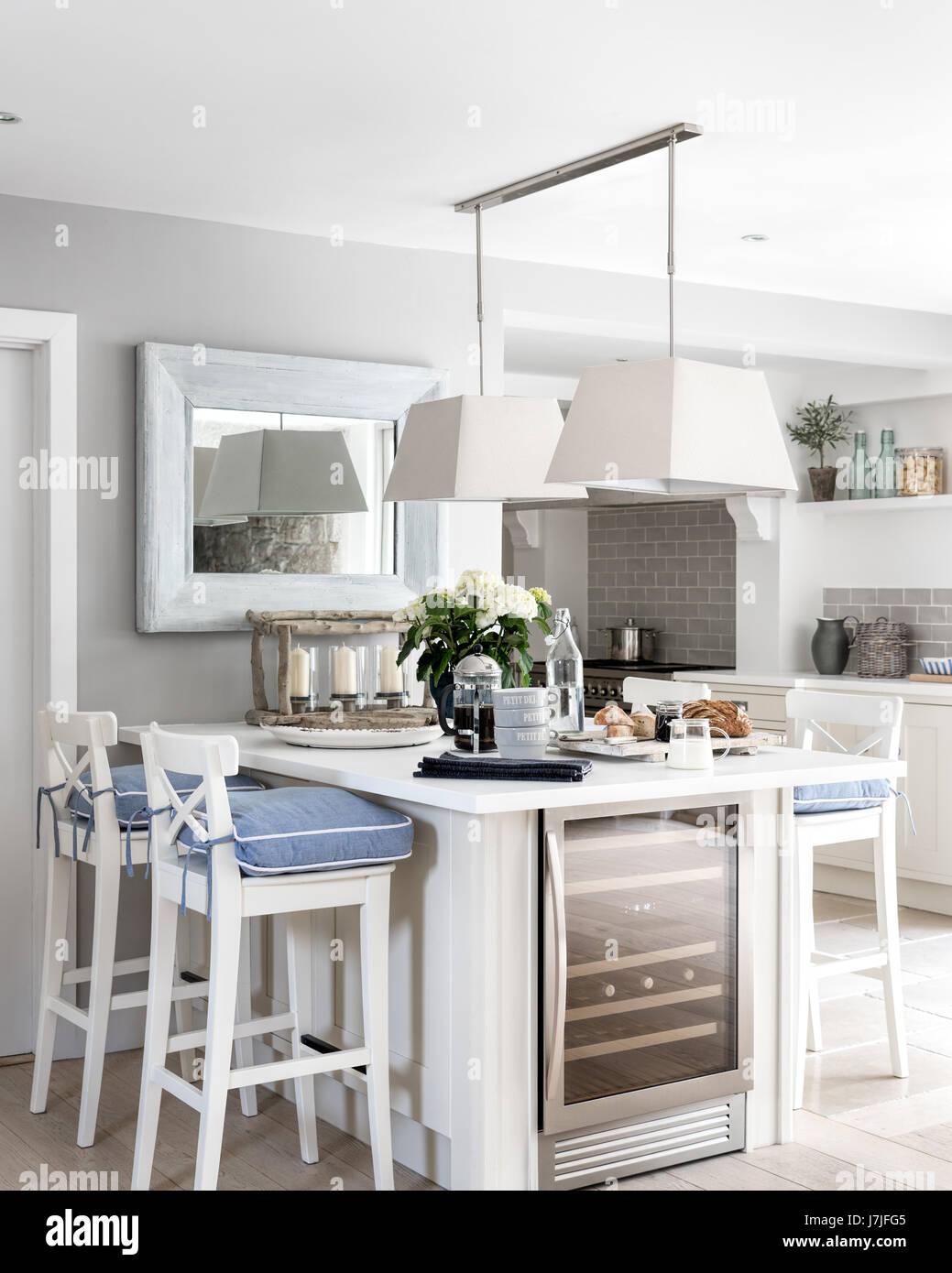Barra de desayuno con blanco Ingolf taburetes de Ikea y las napas jaspeado blanco de la compañía. El colgante luces Foto de stock