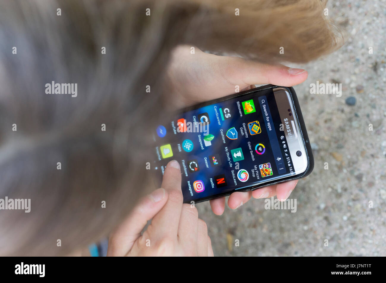 Una niña utilizando la pantalla táctil del teléfono móvil / smartphone apps Imagen De Stock