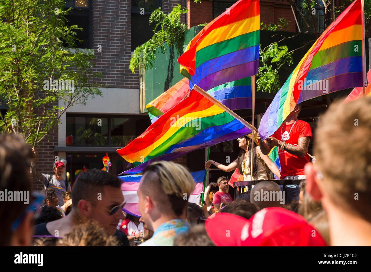 La CIUDAD DE NUEVA YORK - Junio 26, 2015: Los partidarios de onda banderas arcoiris al margen del Desfile del Orgullo Imagen De Stock