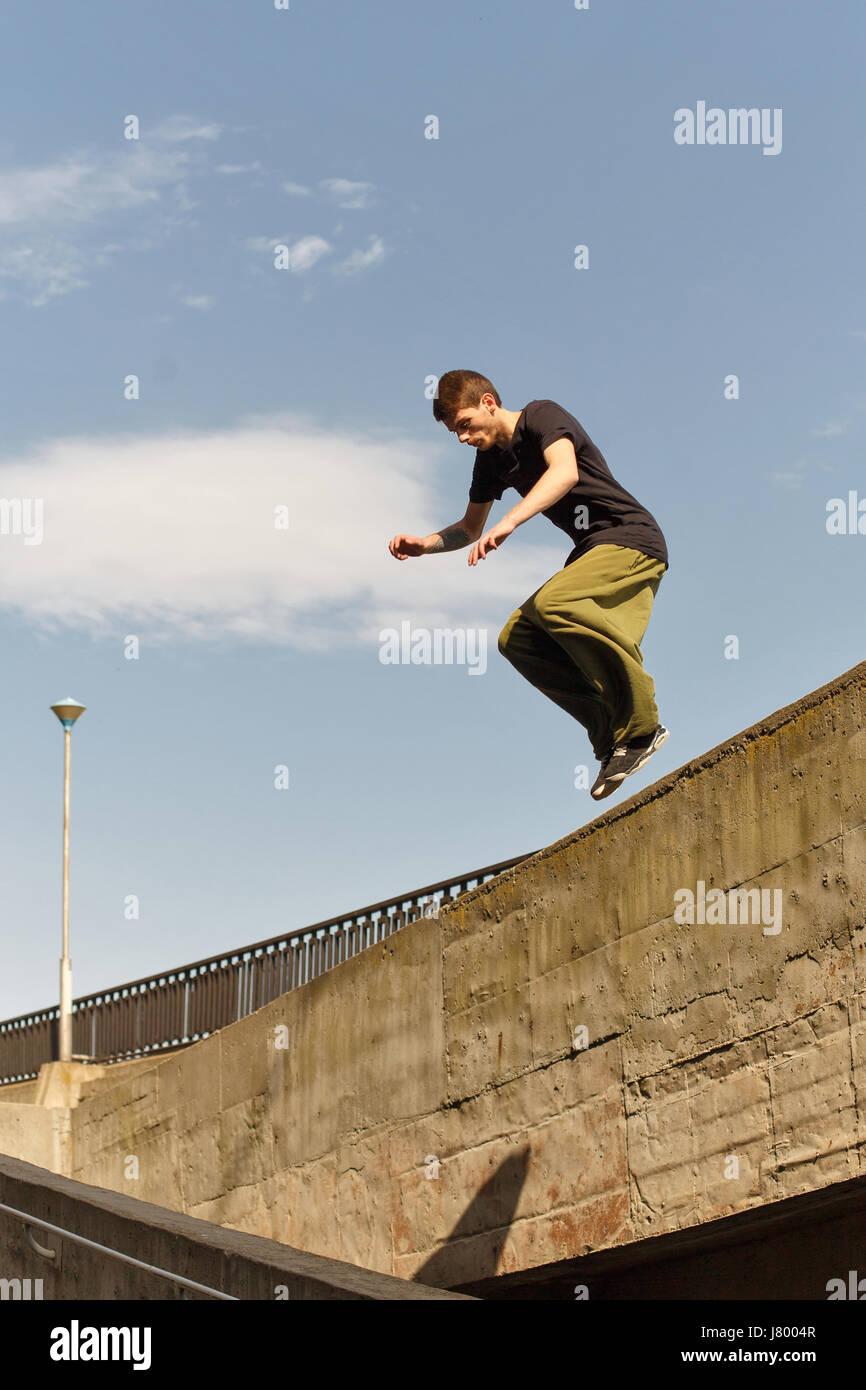 Un joven está saltando desde un muro alto. Parkour en el espacio urbano. El deporte en la ciudad. Actividades Imagen De Stock