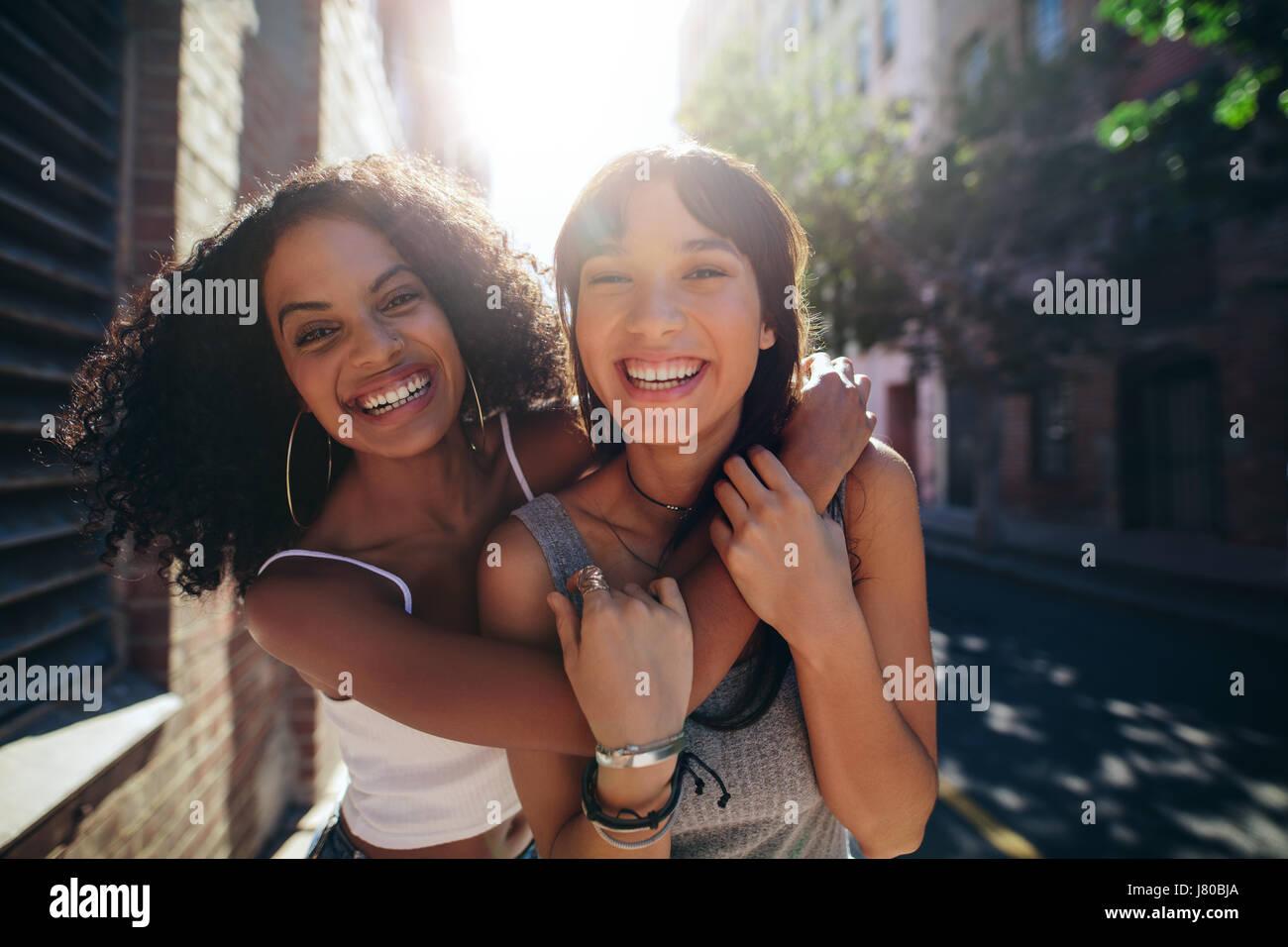 Retrato de dos mujeres jóvenes en las calles de la ciudad para divertirse. Amigas en la carretera abrazar y Imagen De Stock