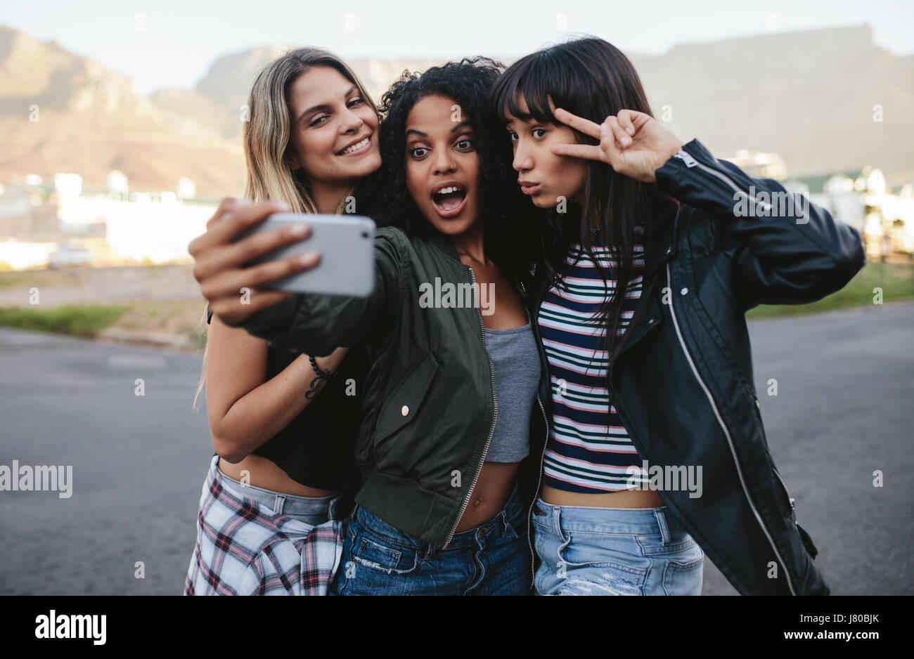 Feliz amigas haciendo selfie con smart phone. Grupo multiétnico de la mujer colgando fuera de la ciudad y tomar Imagen De Stock