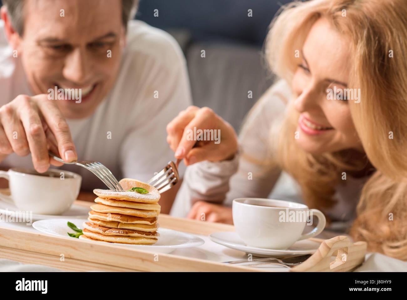 Feliz pareja de mediana edad comer panqueques juntos en la cama Imagen De Stock