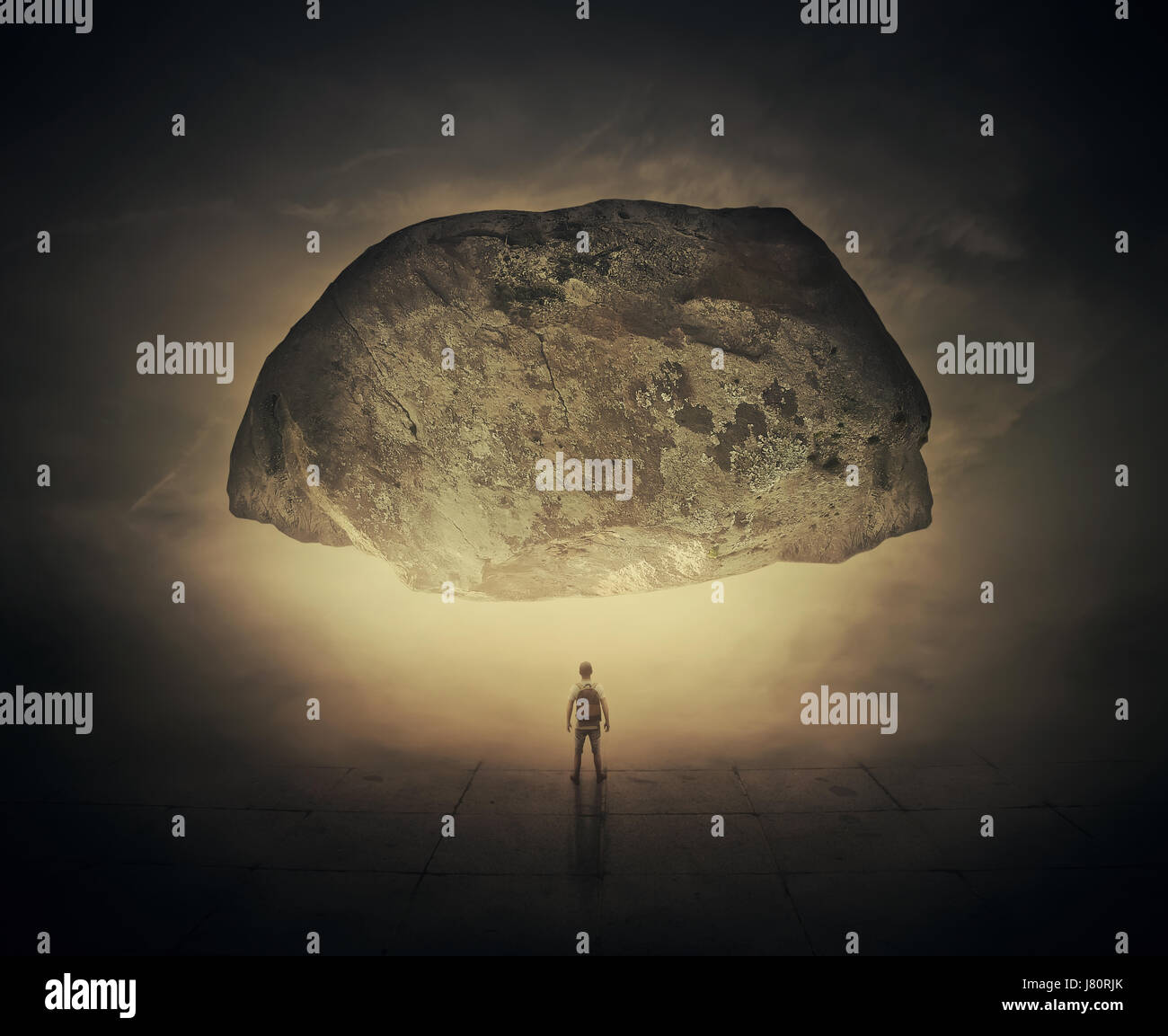 Imagen surrealista como un hombre con una bolsa en la espalda, en un stand foggy calle debajo de una enorme roca Foto de stock