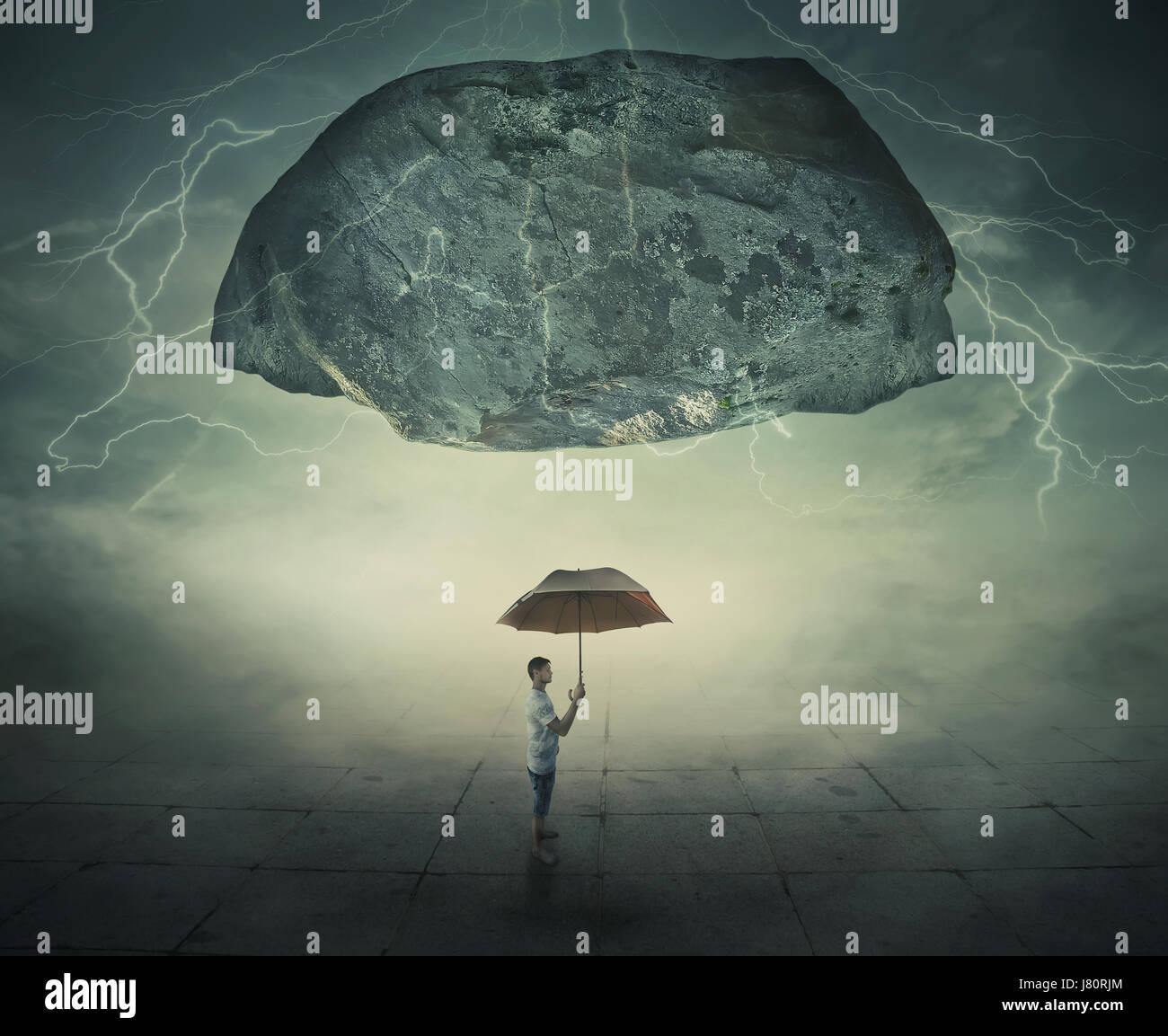 Imagen surrealista como un hombre de pie en una calle neblinosa bajo una enorme roca levitante, sosteniendo un paraguas Foto de stock