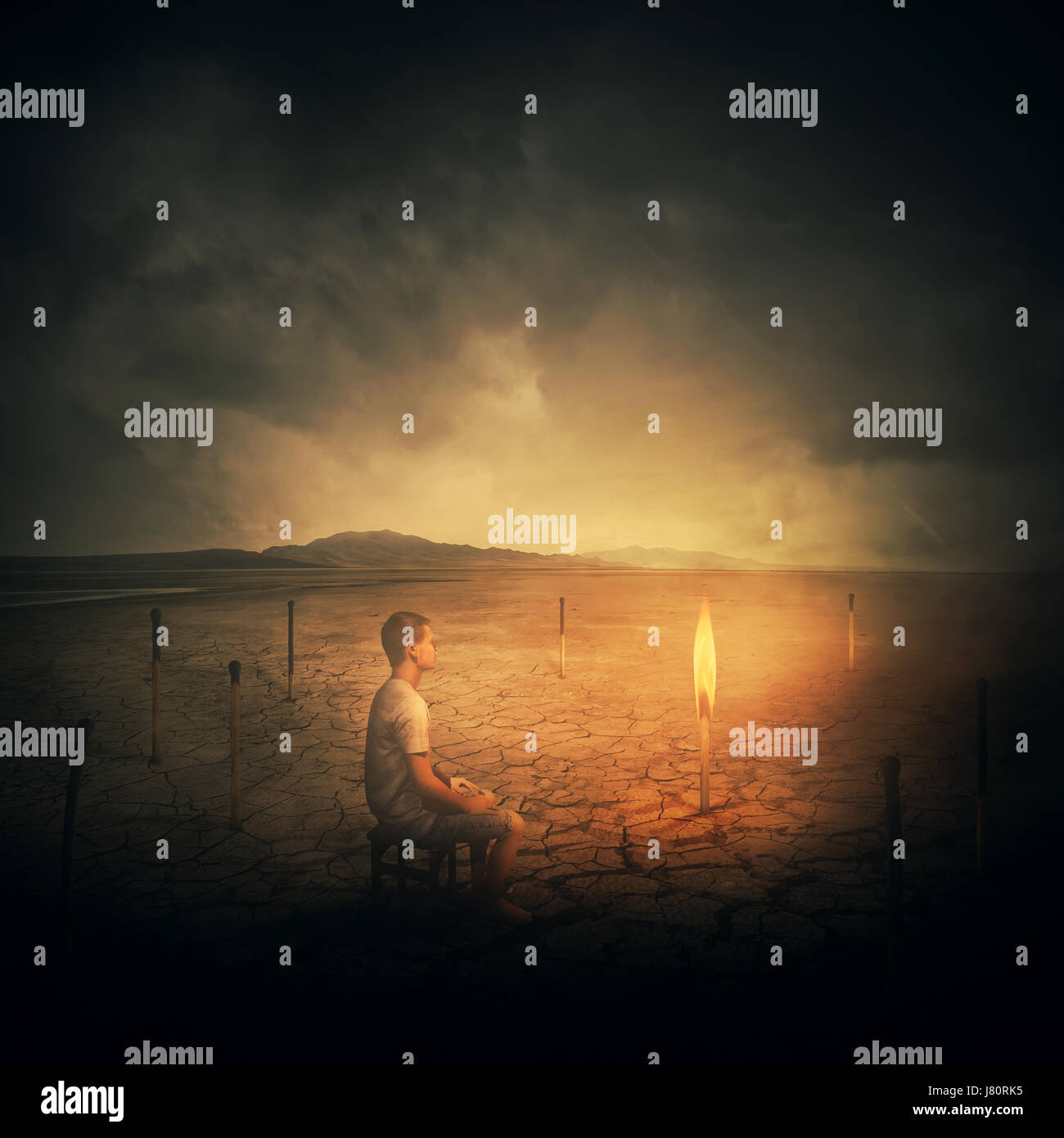 Concepto surrealista como un hombre, sentado en una silla en el medio del desierto, mirando a una sola quema matchstick Foto de stock