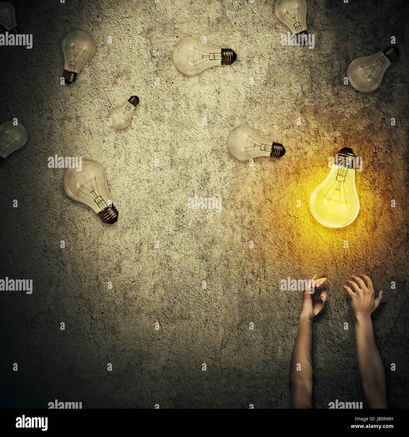 Concepto como idea abstracta las manos estiradas y hacer malabares con un montón de bombillas, uno de ellos brillando. Foto de stock