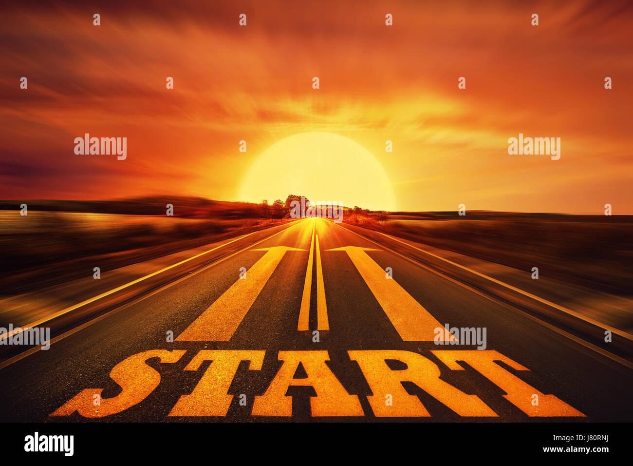 Inicio de palabra escrita en una carretera asfaltada y dos flechas como motivación. Largo camino por delante como Foto de stock