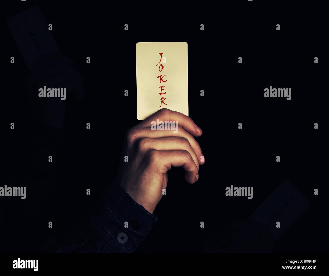 Cerca de la mano de un hombre sosteniendo joker naipe. Ilusionista mostrando un truco de magia sobre un fondo negro. Foto de stock
