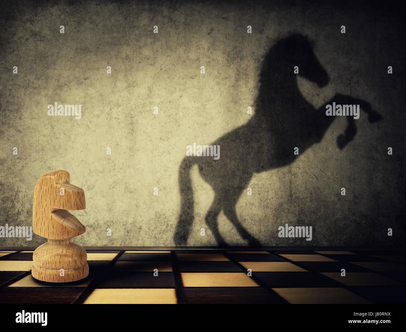 Transformación mágica como una pieza de ajedrez Knight de madera una sombra de un caballo salvaje sobre dos piernas Foto de stock
