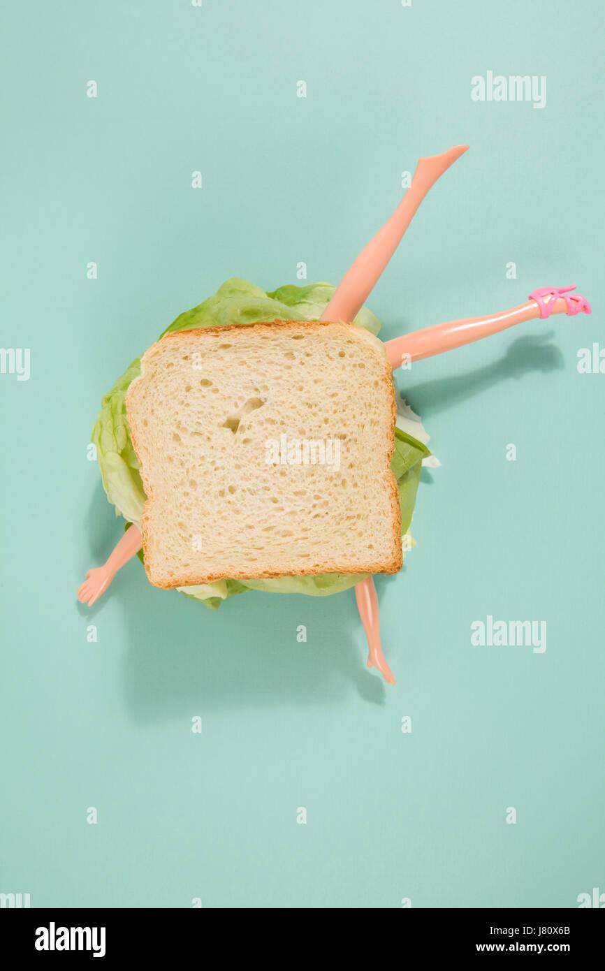 Partes de un cuerpo de muñeca en un sándwich con ensalada y pan blando sobre un fondo de color mínima. Imagen De Stock