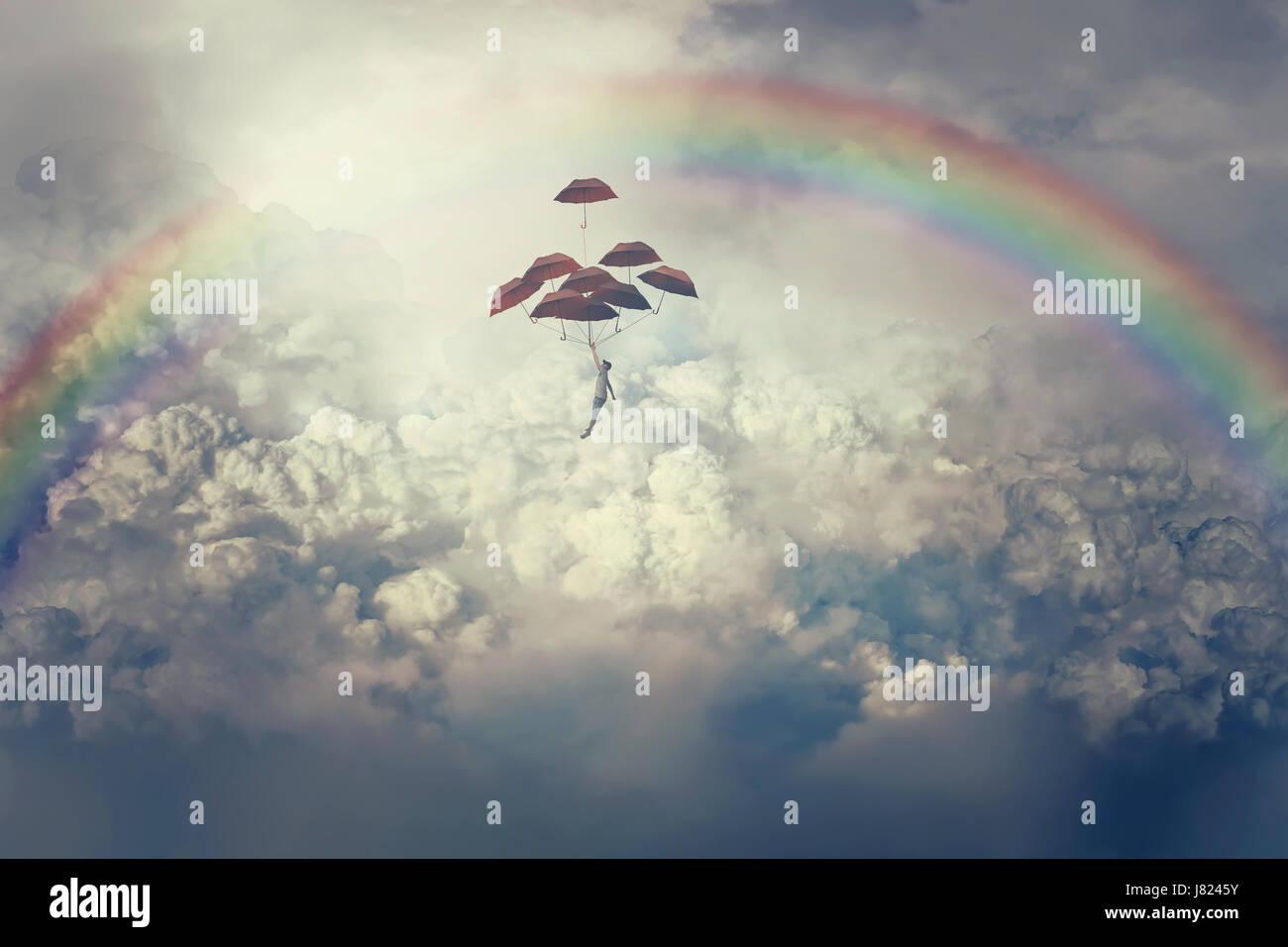 Vista imaginaria con un joven niño volando por encima de las nubes sosteniendo un montón de paraguas. En el camino Foto de stock