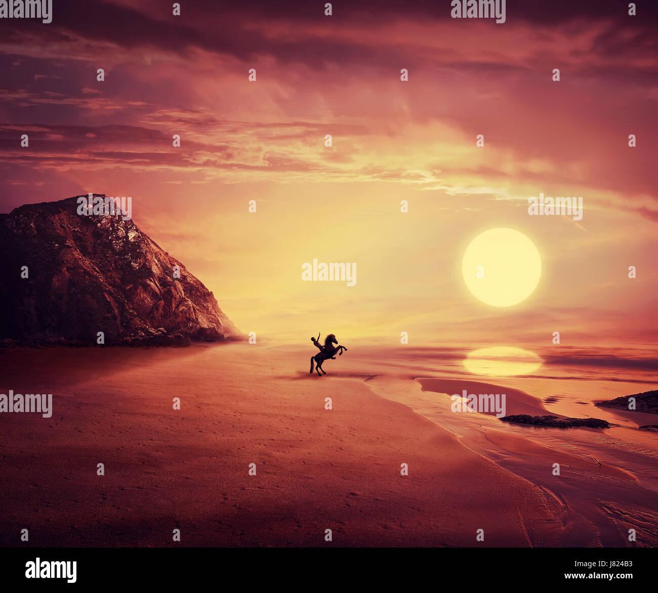 Joven montando un caballo salvaje cerca de la orilla del mar a través de una puesta de sol caliente de fondo. El Foto de stock