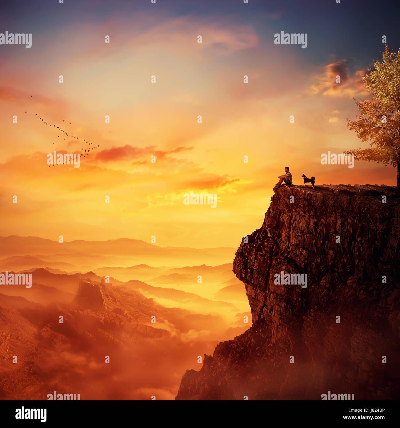 Joven con su fiel perro parado en la cima de un acantilado mirando el atardecer sobre el valle. Recordando recuerdos Foto de stock