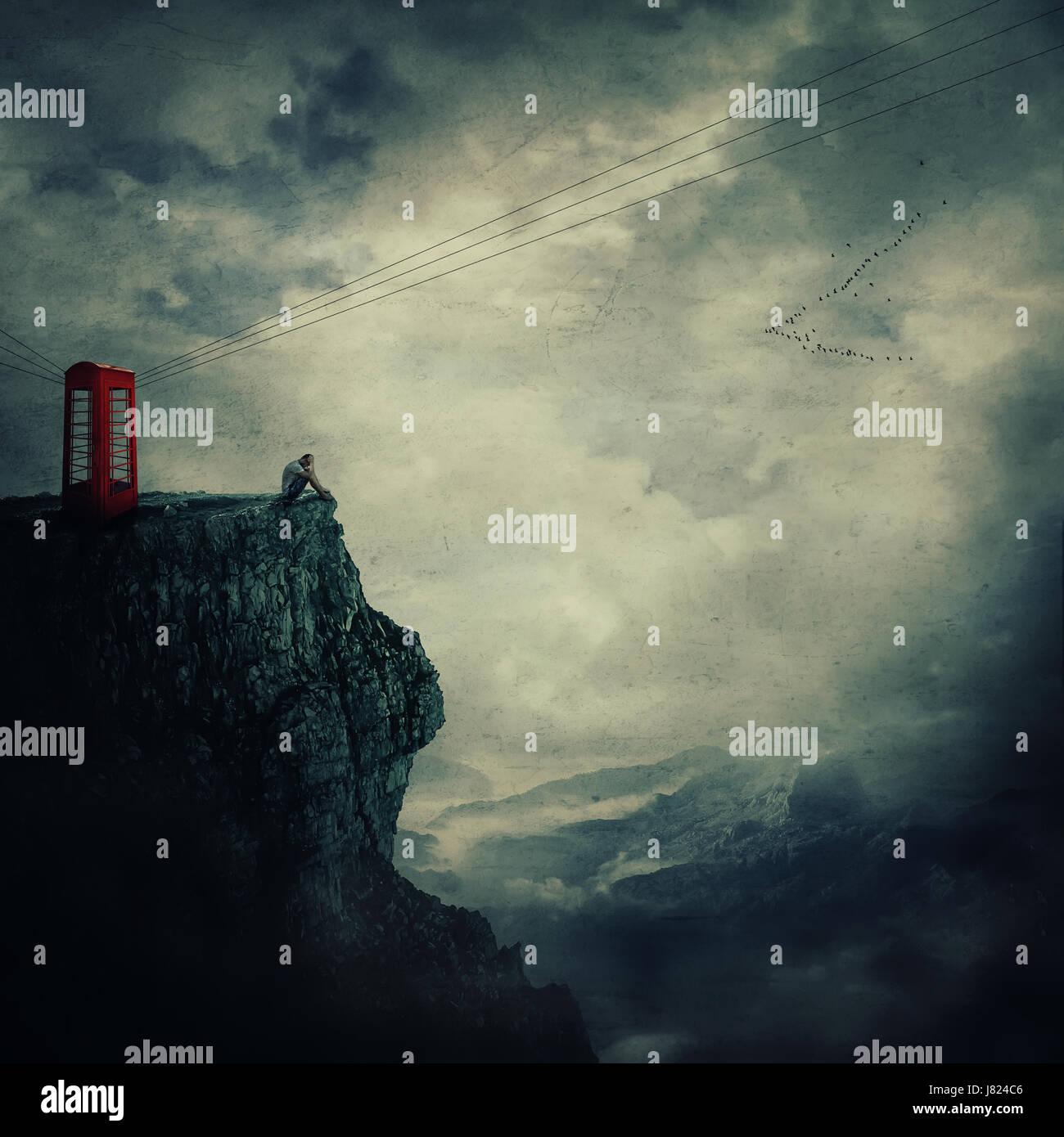 Vista surrealista como un triste, joven, de pie en el borde de un acantilado cerca de una caja de teléfono rojo, Foto de stock