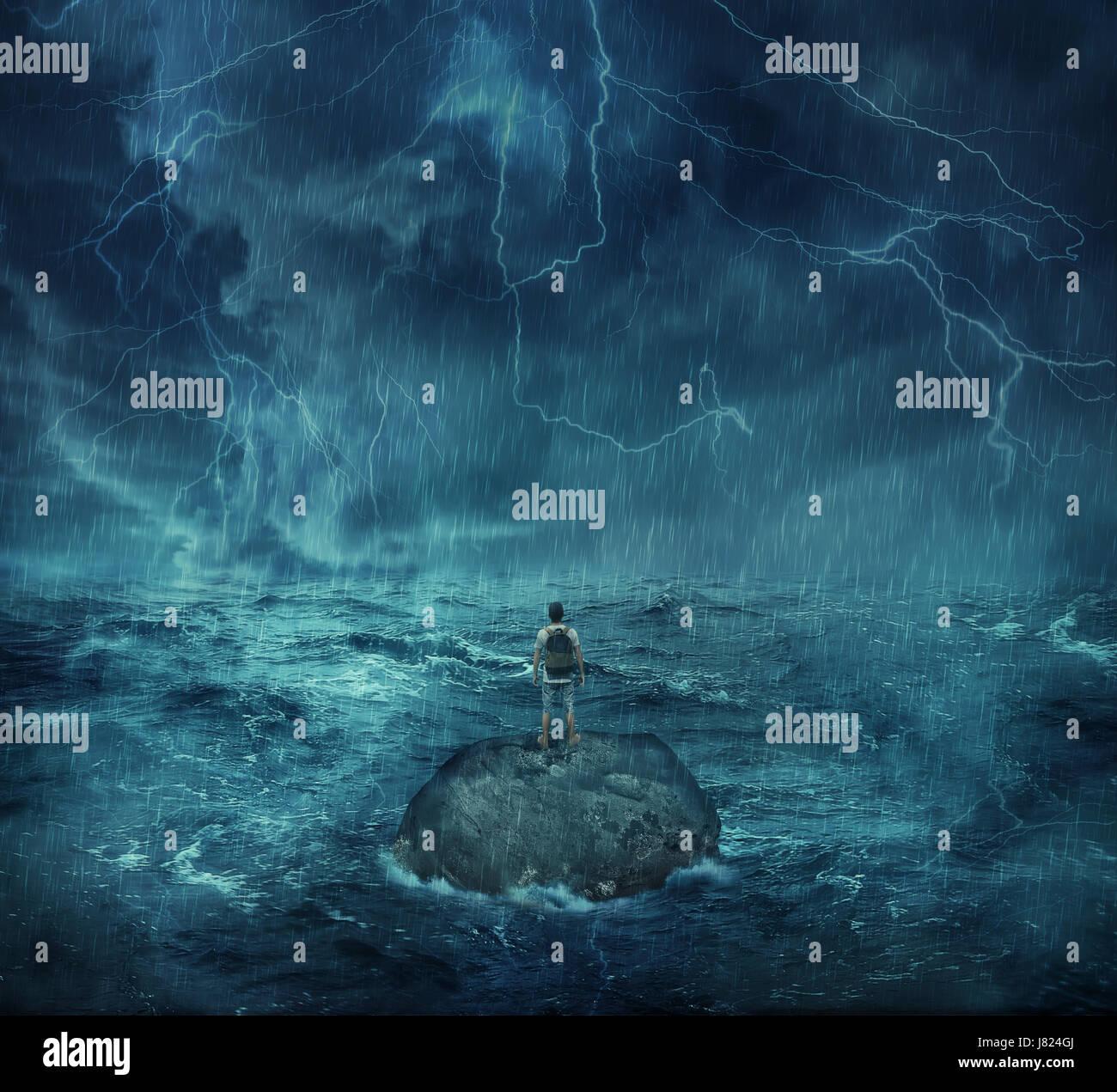 Perdido man standing abandonado en una isla de roca en medio del océano, en una noche de tormenta con relámpagos Foto de stock