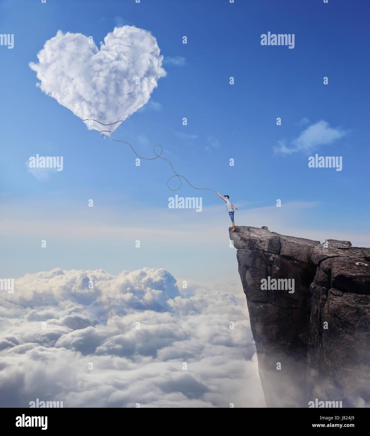 Vista imaginaria con un muchacho al borde de un acantilado, intentando coger una nube en forma de corazón con una Foto de stock
