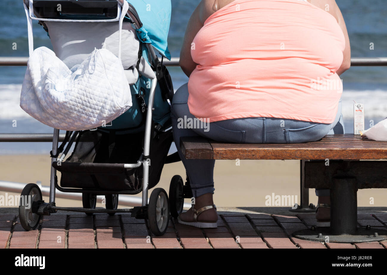 Obesa mujer sentada en un banco con vistas al mar. Imagen De Stock