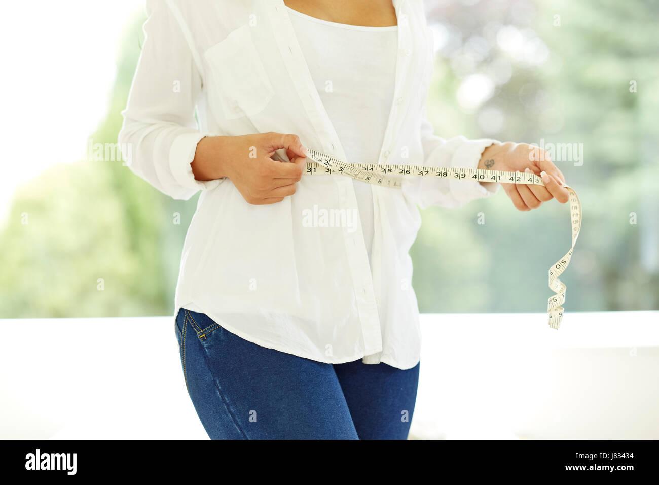 Mujer sosteniendo una cinta métrica alrededor de su cintura Imagen De Stock