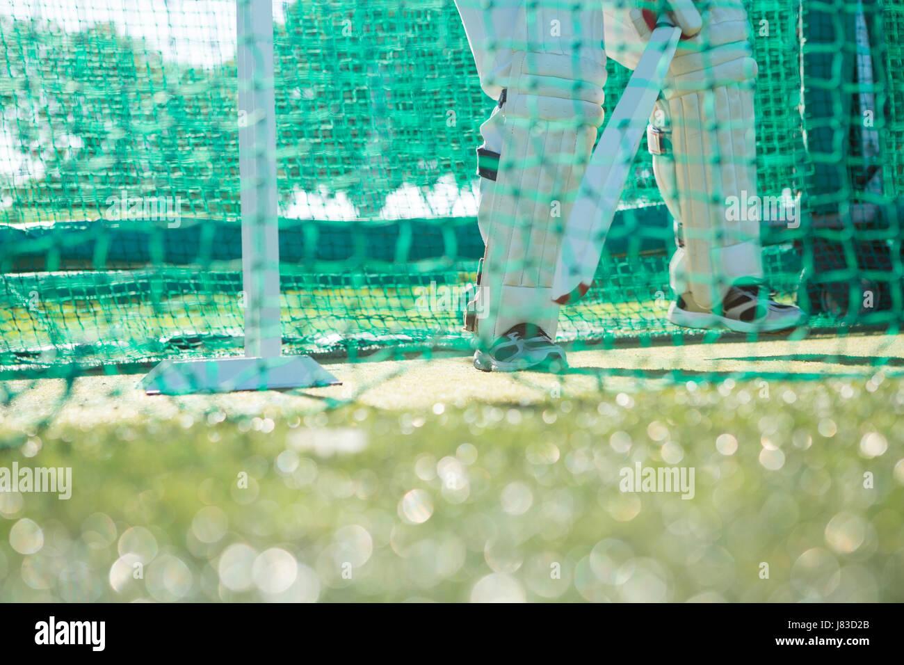 Bajo la sección del hombre jugando críquet estando de pie en el campo de deportes Imagen De Stock