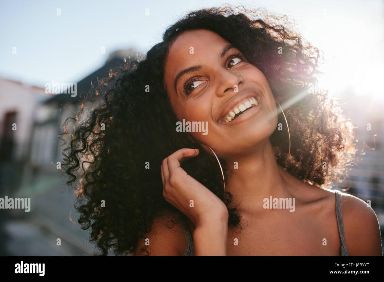 Cerrar retrato del joven africana con el pelo rizado mirando a otro lado. Mujer Afro americana de pie afuera y sonriente. Imagen De Stock