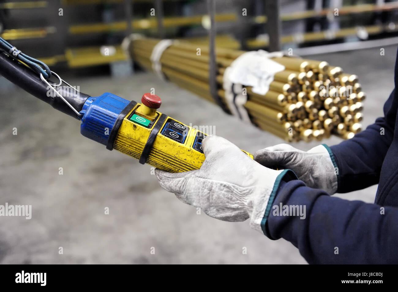 Close-up de trabajador en manos Guantes manipulación de puente grúa interior de fábrica pulsando Imagen De Stock