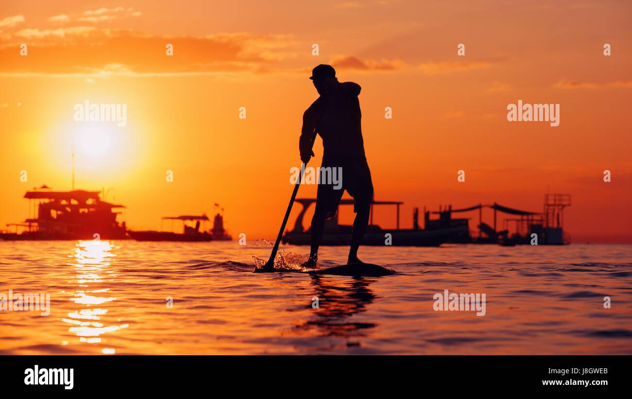 Paleta activa boarder. Sunset silueta negra del joven deportista remando en stand up paddleboard. Estilo de vida Foto de stock
