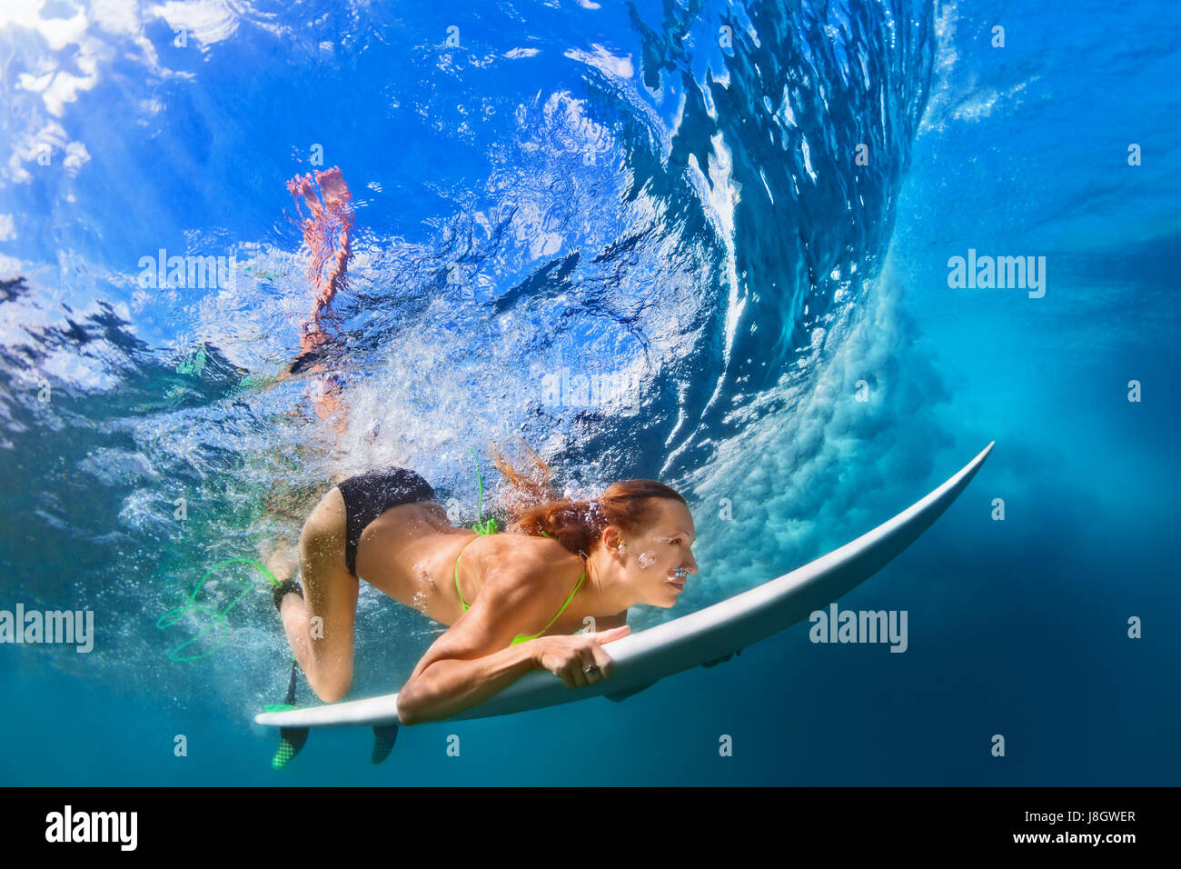 Active chica en bikini en acción. Surfer mujer con surf buceo bajo submarino Rompiendo olas grandes. Estilo Imagen De Stock