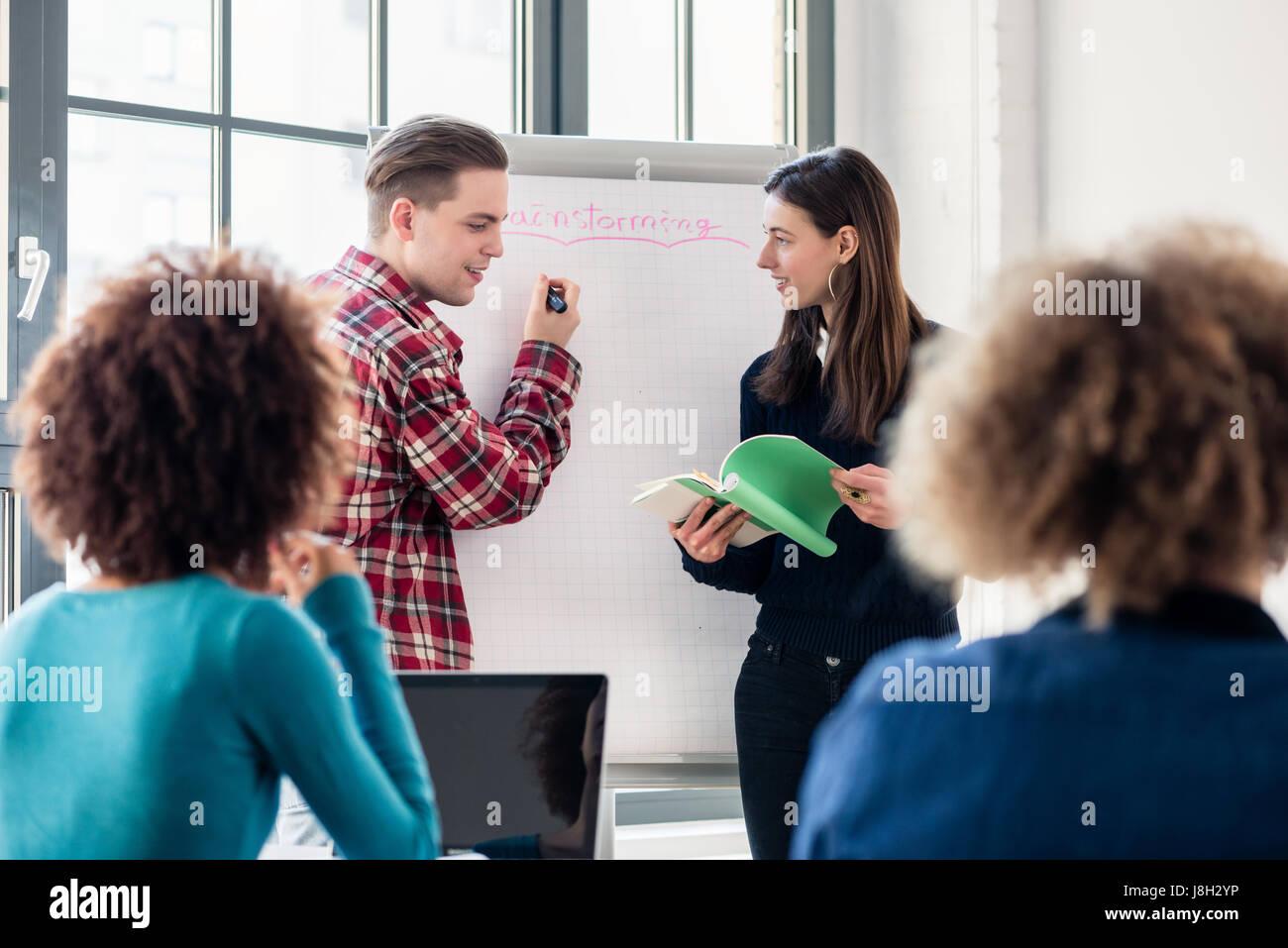 Los estudiantes que comparten ideas y opiniones mientras durante una lluvia de ideas Imagen De Stock