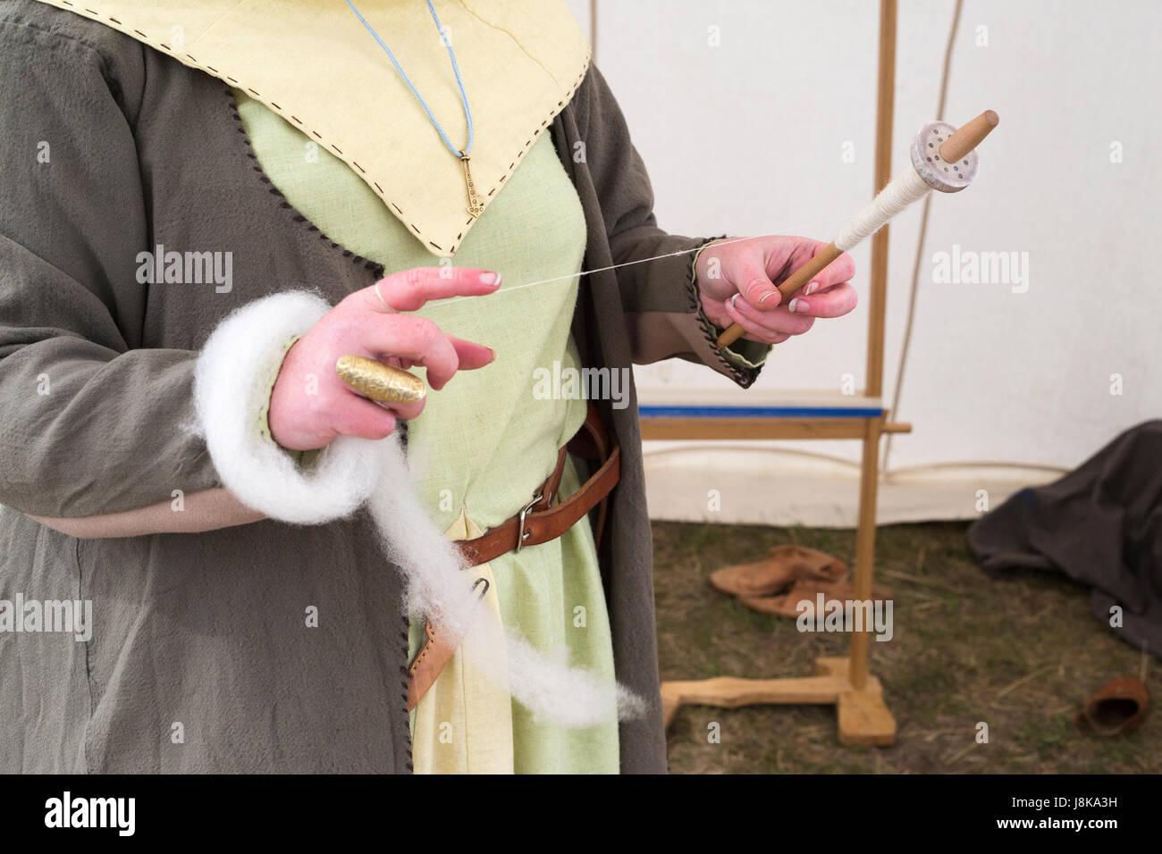 Mujer vestida con traje tradicional hilando lana en carpa en la réplica del asentamiento vikingo Imagen De Stock