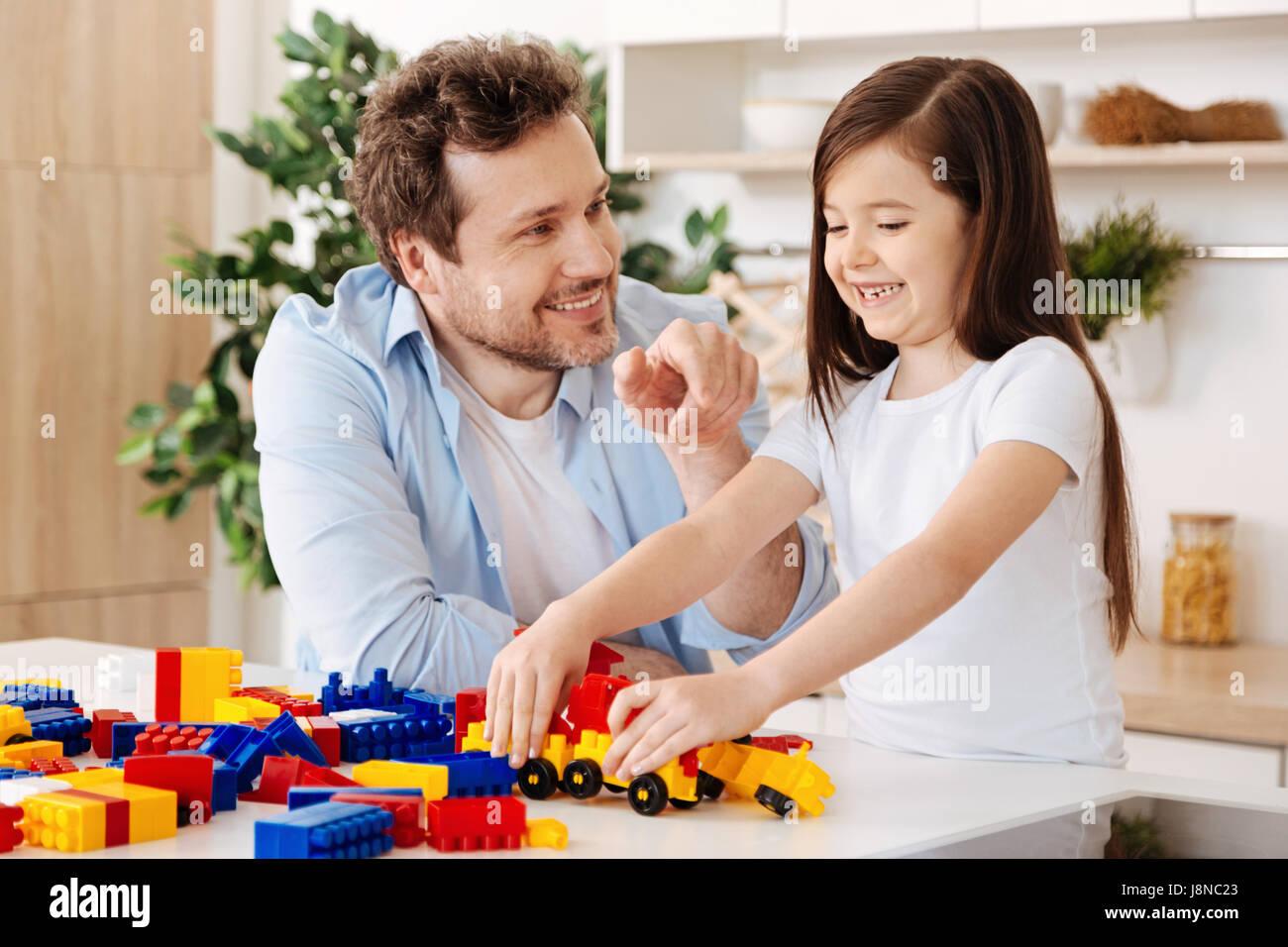 Sinceros sentimientos. Agradable alegre padre y su pequeña hija gozoso mirando feliz y sonriente mientras la Imagen De Stock
