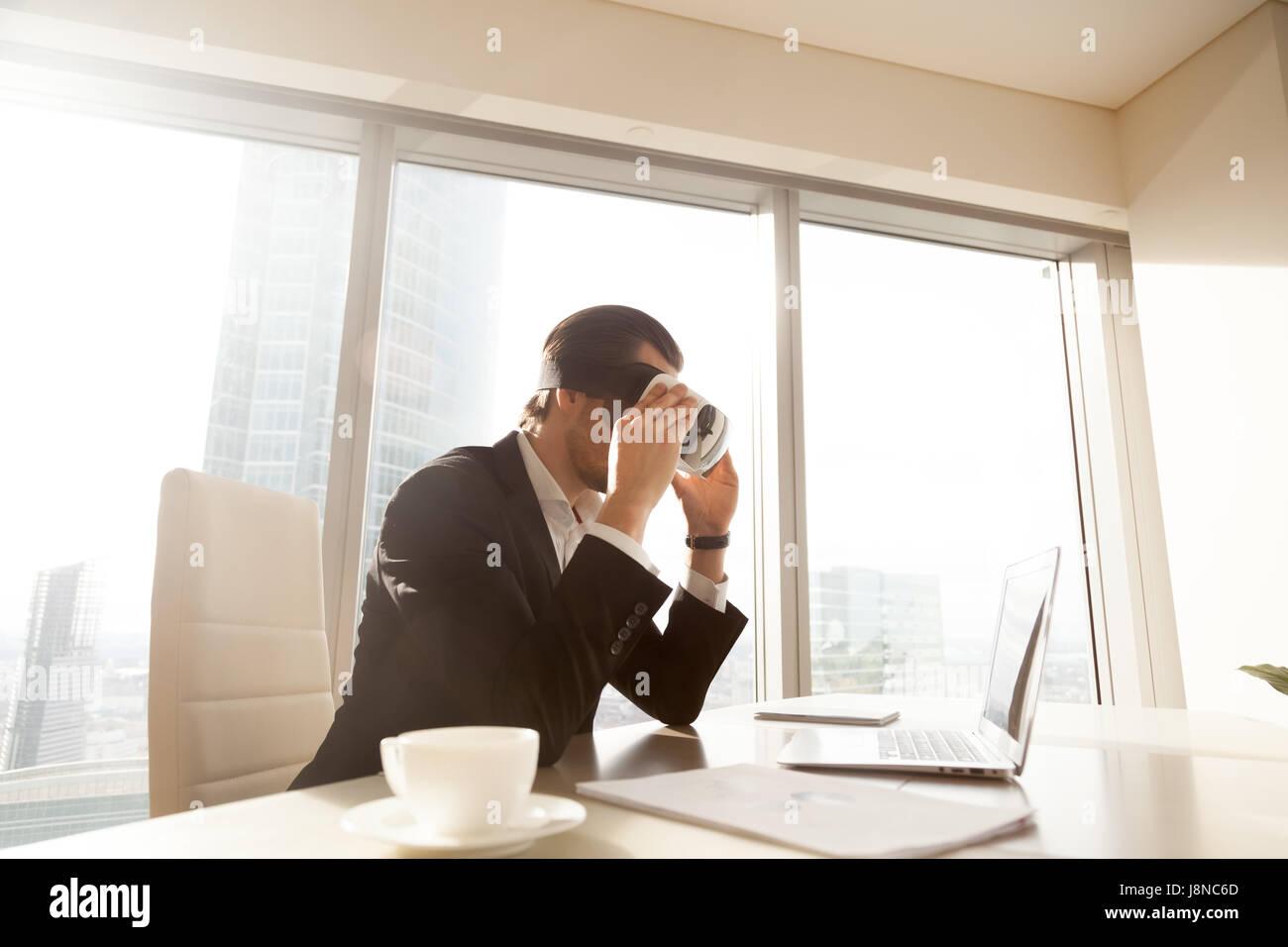 Hombre mirando la pantalla de un ordenador portátil a través de auriculares VR Foto de stock