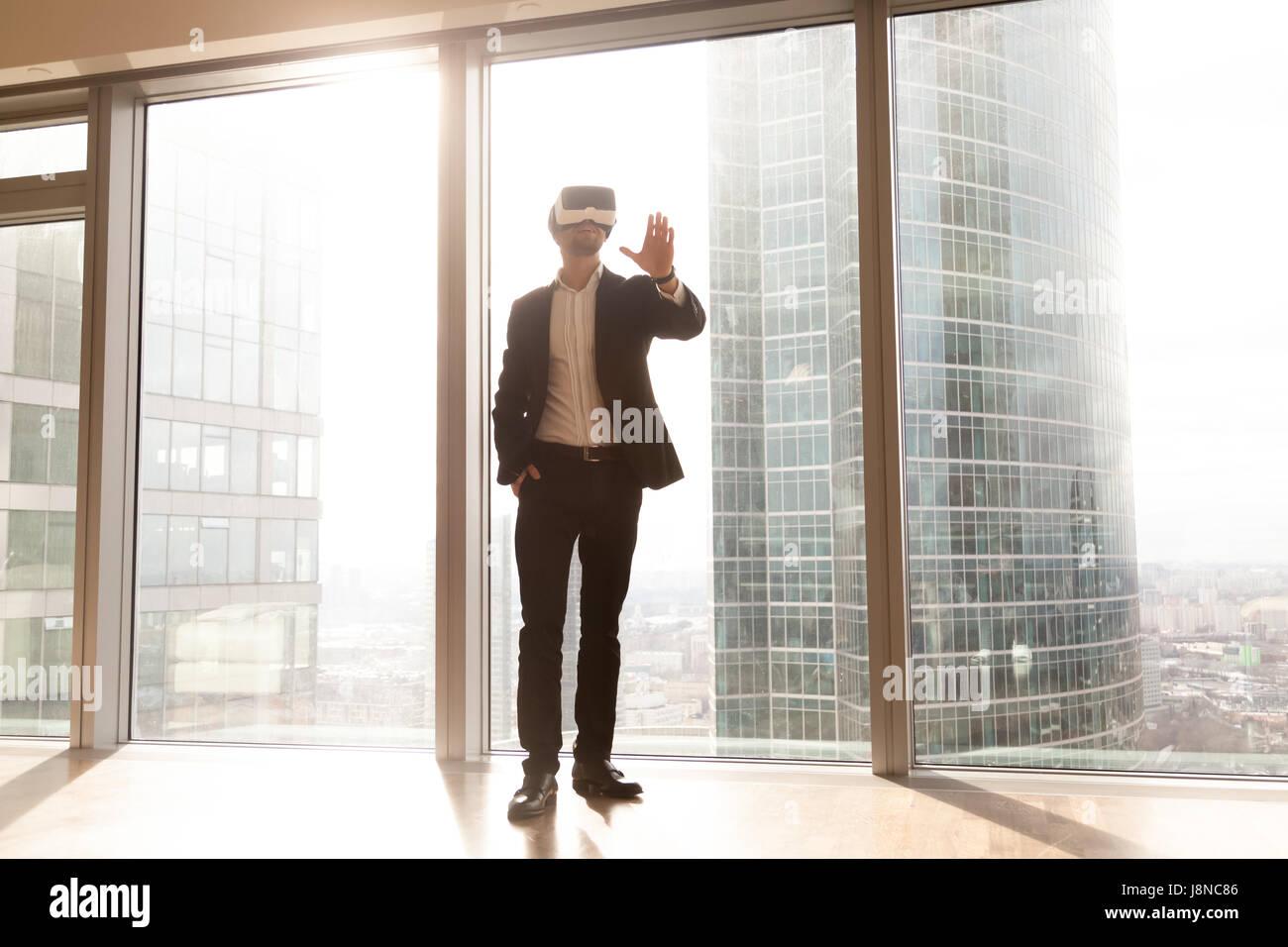 Hombre en auricular VR goza de visualización 3D interior Imagen De Stock