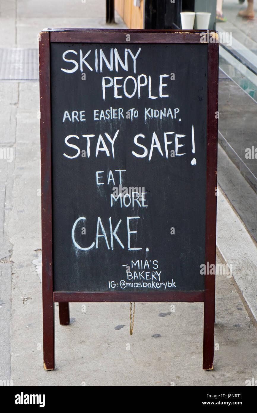 Un signo muy divertido fuera de Mia panadería en la calle Smith en la colina Coblle alentando a la gente a comer más pastel. Brooklyn, Nueva York Foto de stock