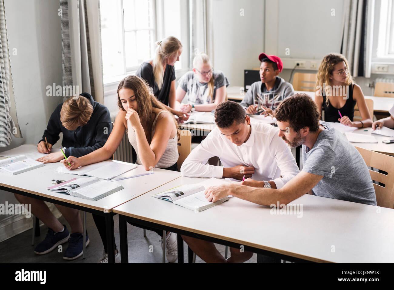 El profesor y los estudiantes (14-15) en el aula Foto de stock