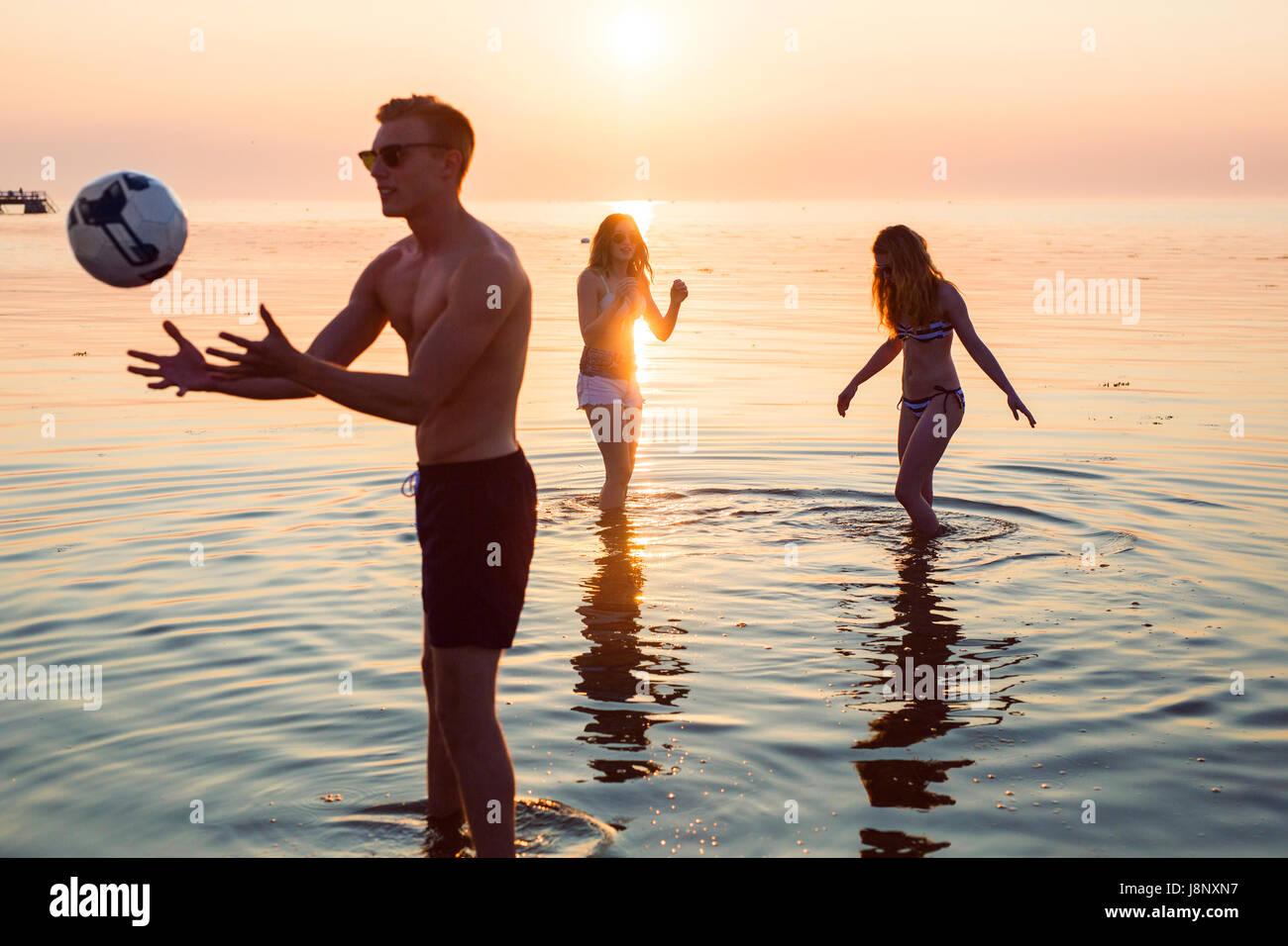 Joven, joven y adolescente (16-17) jugando voleibol en el mar al atardecer Foto de stock