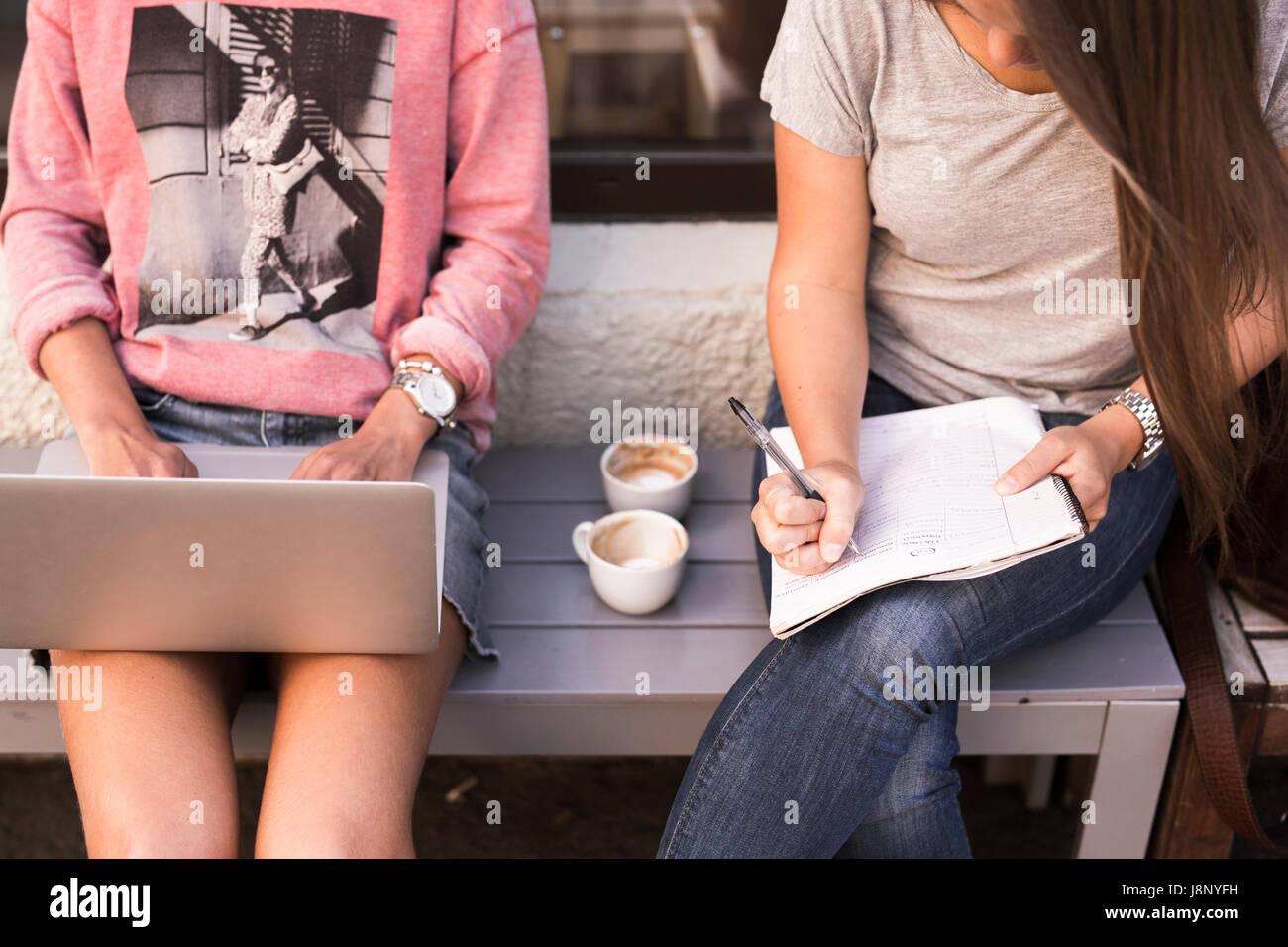 Las mujeres jóvenes que estudian y utilización portátil Foto de stock