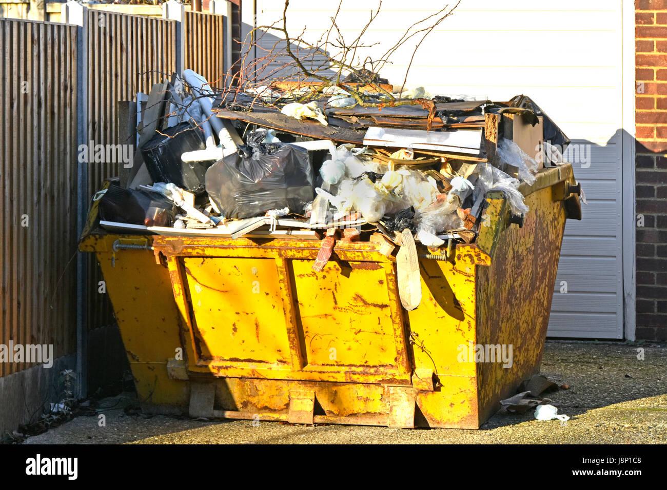 Full UK skip bin logística gestión de residuos del Reino Unido basura basura basura rebosante esperando Imagen De Stock