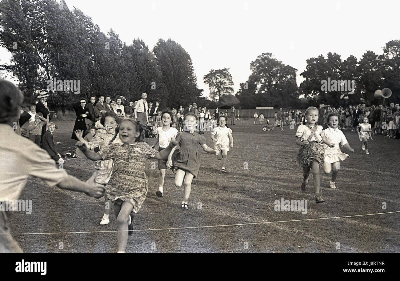 1950. históricas, las niñas corriendo en el 60 yard dash en un día de deportes de la escuela, con un joven alegre Foto de stock