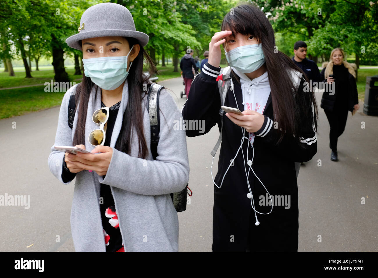 Dos jóvenes mujeres asiáticas llevar mascarillas de contaminación en un parque de Londres, Inglaterra, Imagen De Stock