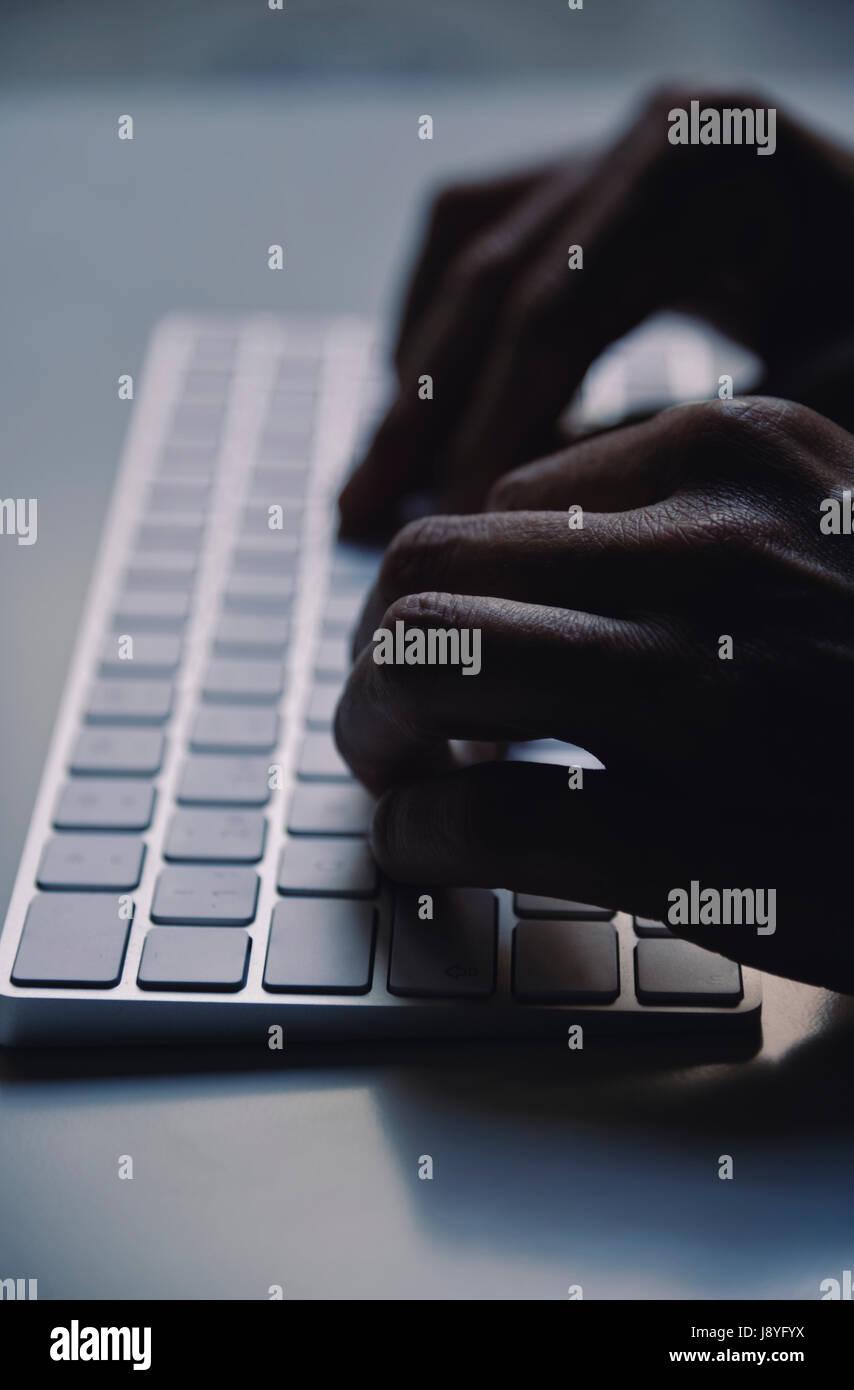 Primer plano de un hombre joven escribiendo en un teclado de ordenador en la oscuridad, con un efecto dramático Imagen De Stock