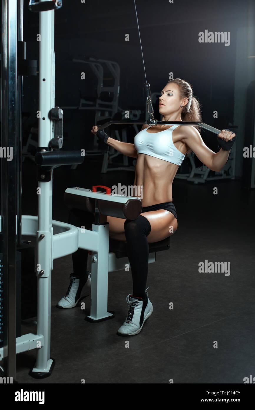 La mujer agita los músculos en el simulador en el gimnasio. Ella un alivio presione el abdomen. Imagen De Stock